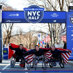 Tatyana McFadden, Manuela Schär, and Susannah Scaroni, the first three finishers of the 2019 United Airlines NYC Half women's wheelchair division, pose with their nation's flags.